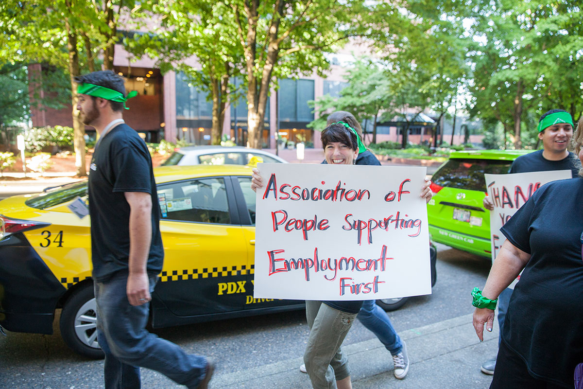 "Woman smiling and walking in the street with a sign that states ""Association of People Supporting Employment First."""