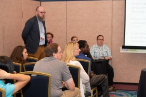 A man standing in front of a breakout session, listening to a person speaking out of frame.