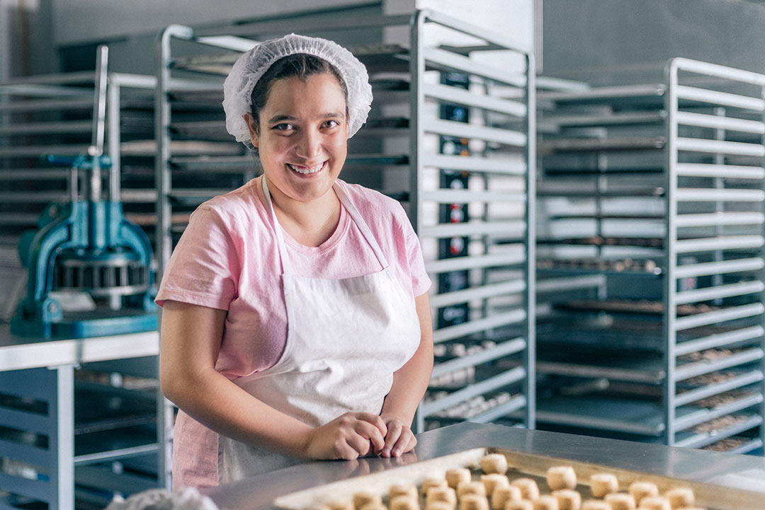 A woman works in a bakery making dough.