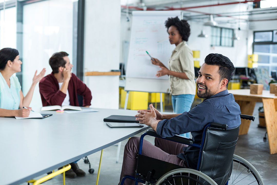 A man in a wheelchair looks at the camera during a meeting with other individuals.