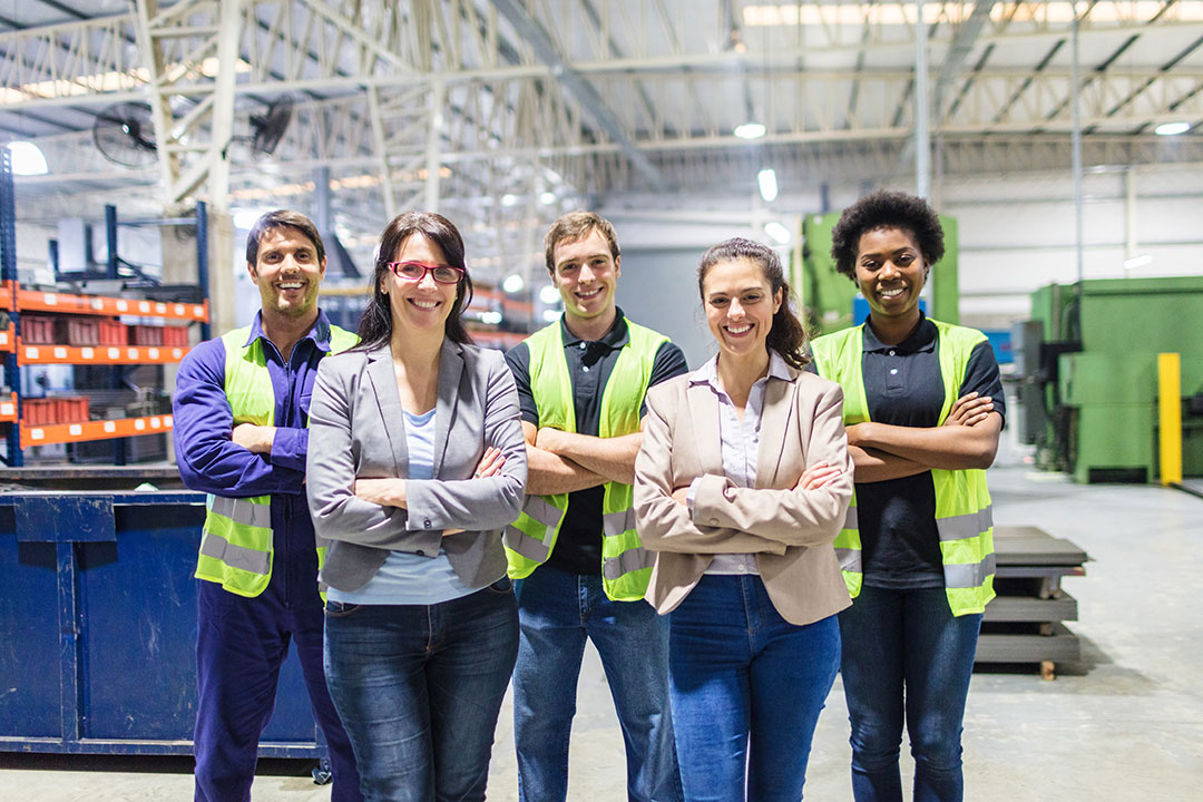 Group portrait of staff at a distribution warehouse. Warehouse team standing with arms crossed in factory.