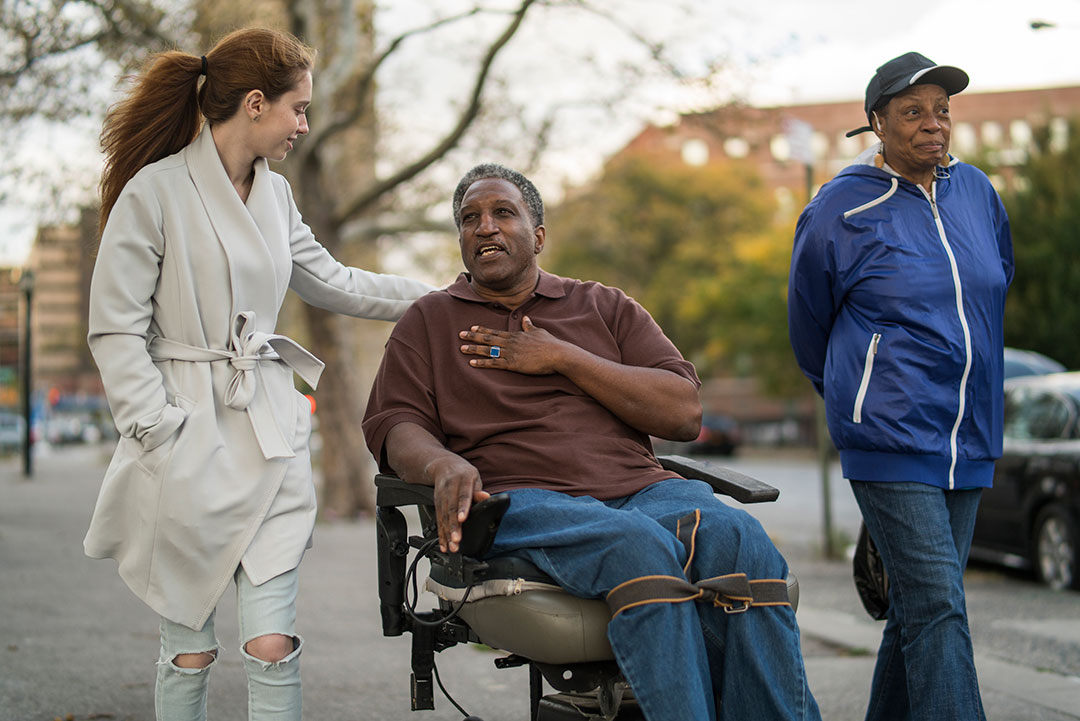 Two women and a man in a wheelchair talk as they are walking down the street.