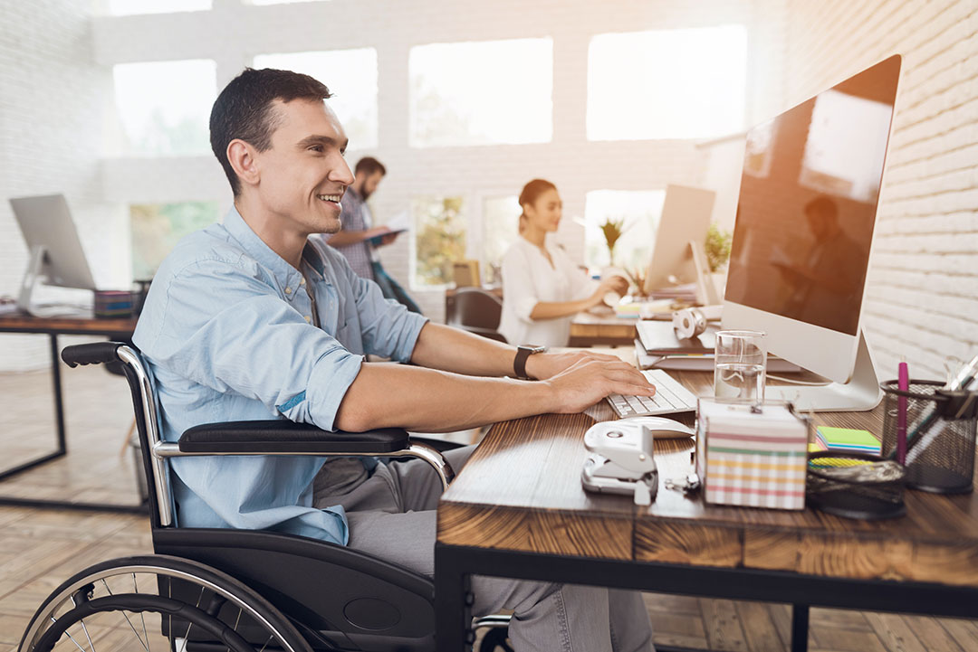 A man in a wheelchair sits at a computer smiling, using the keyboard.