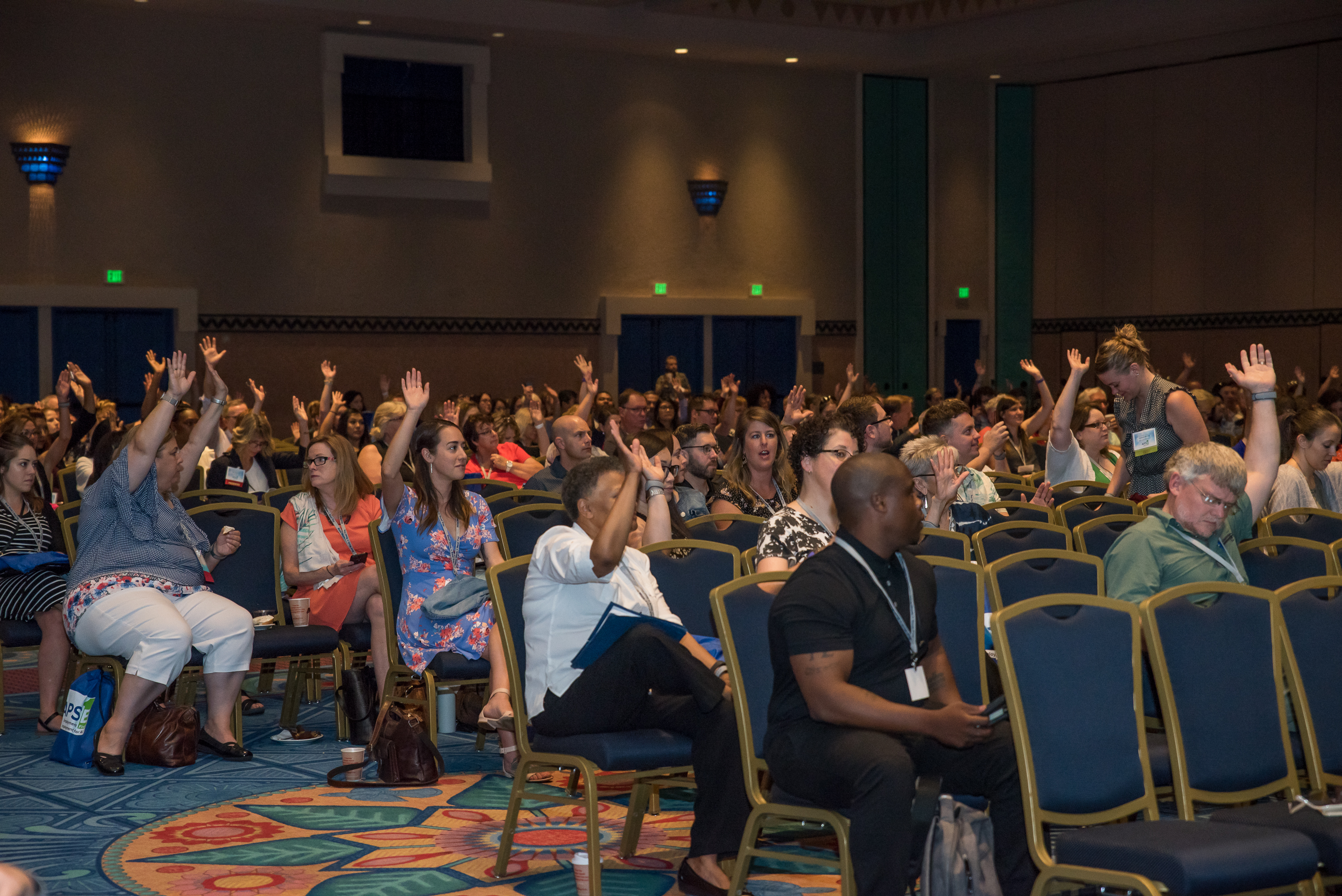 Large group session with attendees with their hands in the air.