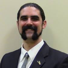 Kie is a white man with black hair and a moustache. He's wearing a suit and smiling.