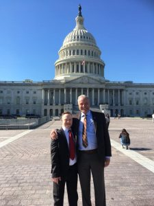 Bill and Kyle stumpf smiling in front of the Washington Capitol in suits.