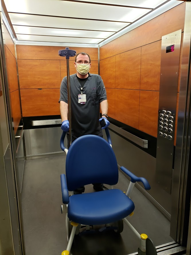 Tommy in a mask pushing a chair in the elevator.