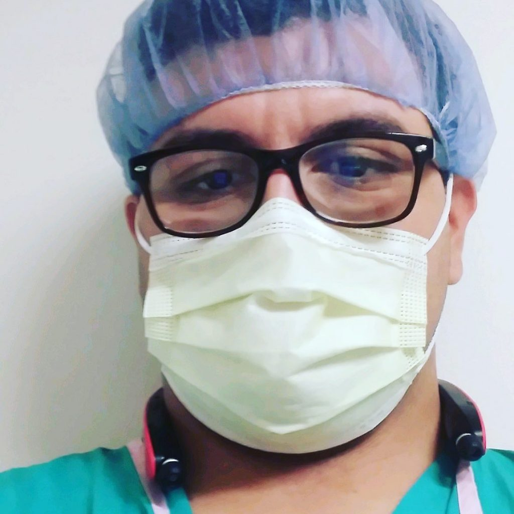 Ulises looking at camera, wearing a mask, glasses, and scrubs.