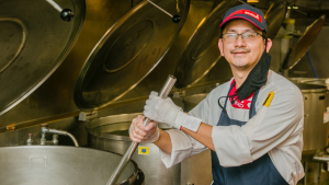 a deafbliind chef stirring a pot of food at work wWhle wearing his uniform.