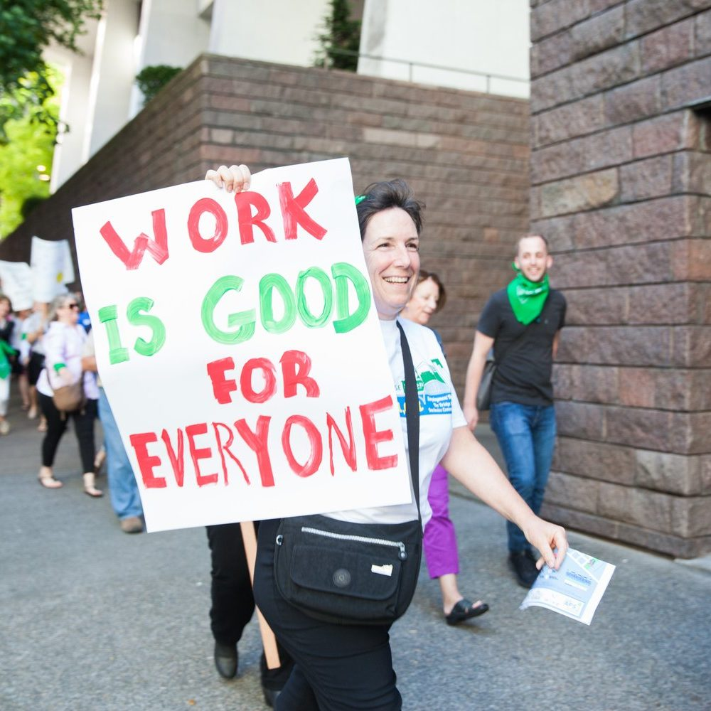 "Woman walking down the street as part of a march, holding a sign that says ""Work is good for everyone."""