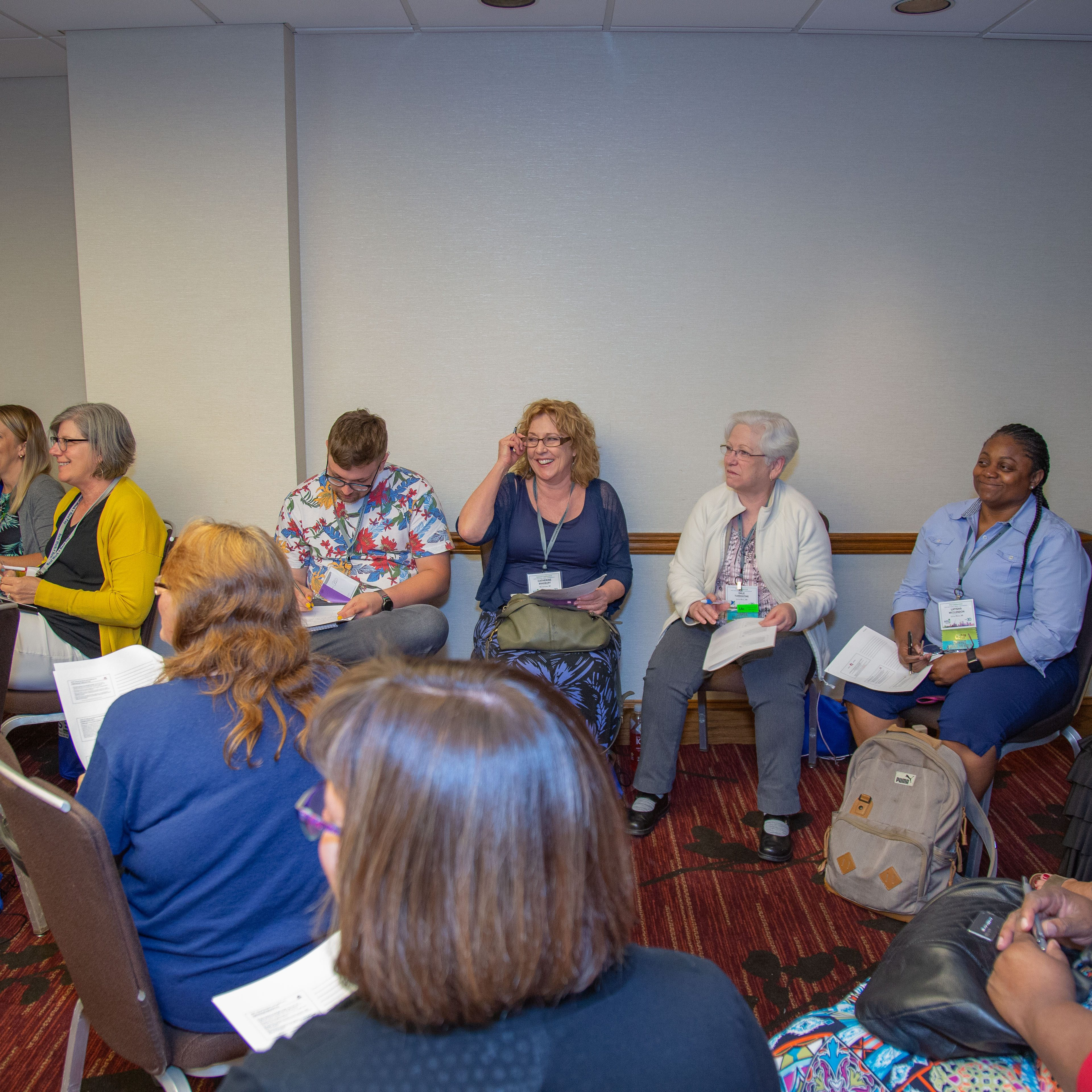 A group in a circle discussing in a breakout session.