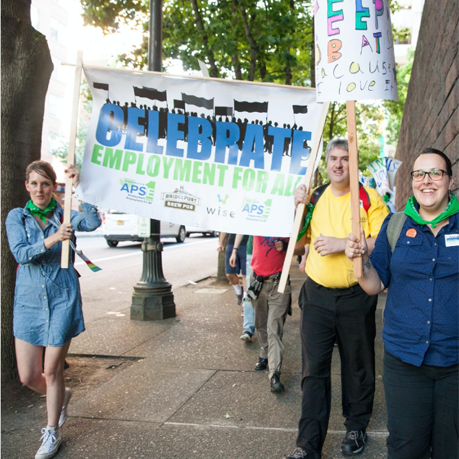"""Three people carrying a flag saying """"Celebrate Employment For All"""" walking down the street."""