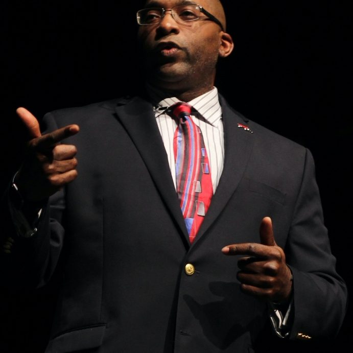 Hasan Davis is a Black man speaking, wearing a suit, tie, and glasses.